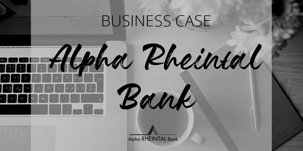 office table with laptop, mug and notebook with the title business case alpha rheintal bank black and white