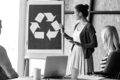 people in a meeting watching a recycling symbol in a board with filter black and white